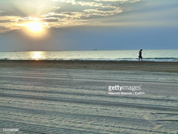 Mid Distance View Of Man Walking At Beach Against Sky During Sunset