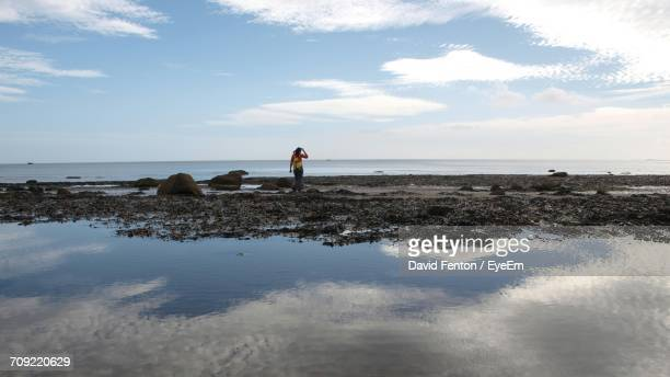 Mid Distance View Of Woman Standing On Sand At Beach
