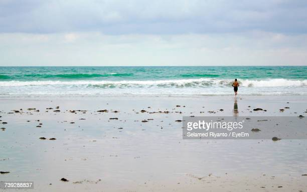 Mid Distant View Of Man Running Towards Sea At Beach Against Sky
