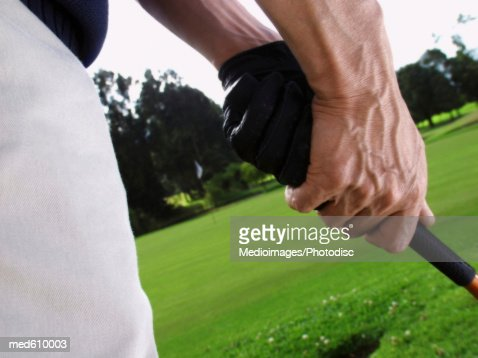 Mid section close-up of golfer getting ready to swing club : Stock Photo