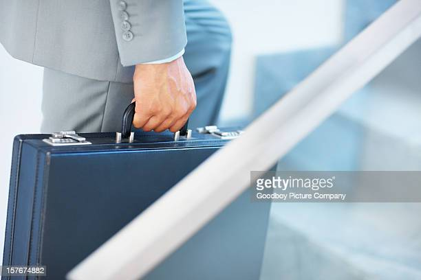 Mid section of a business man walking upstairs with briefcase