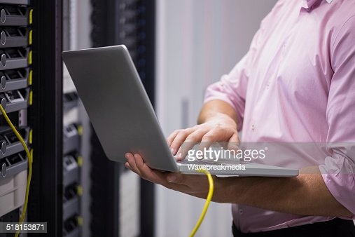 Mid section of a technician typing on his notebook : Stock Photo