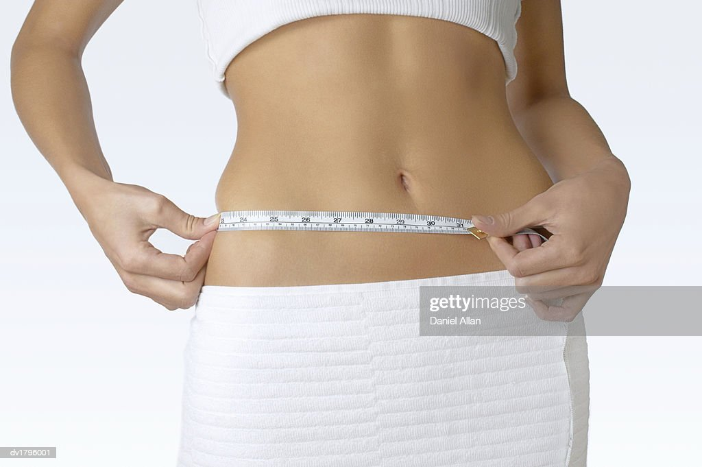 Mid Section of a Woman Measuring her Waist : Stock Photo