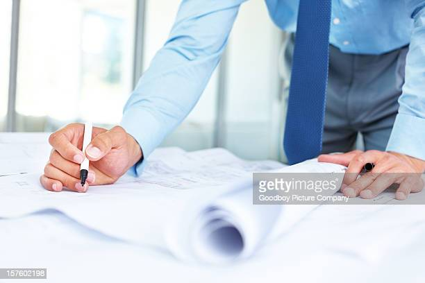 Mid section of a young architect working on blueprints