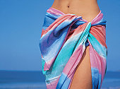 Mid section of a young woman wearing a sarong at the beach