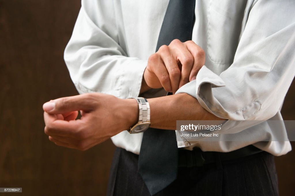 Mid section of businessman rolling sleeves up