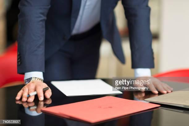 Mid section of businessmans hands on office desk