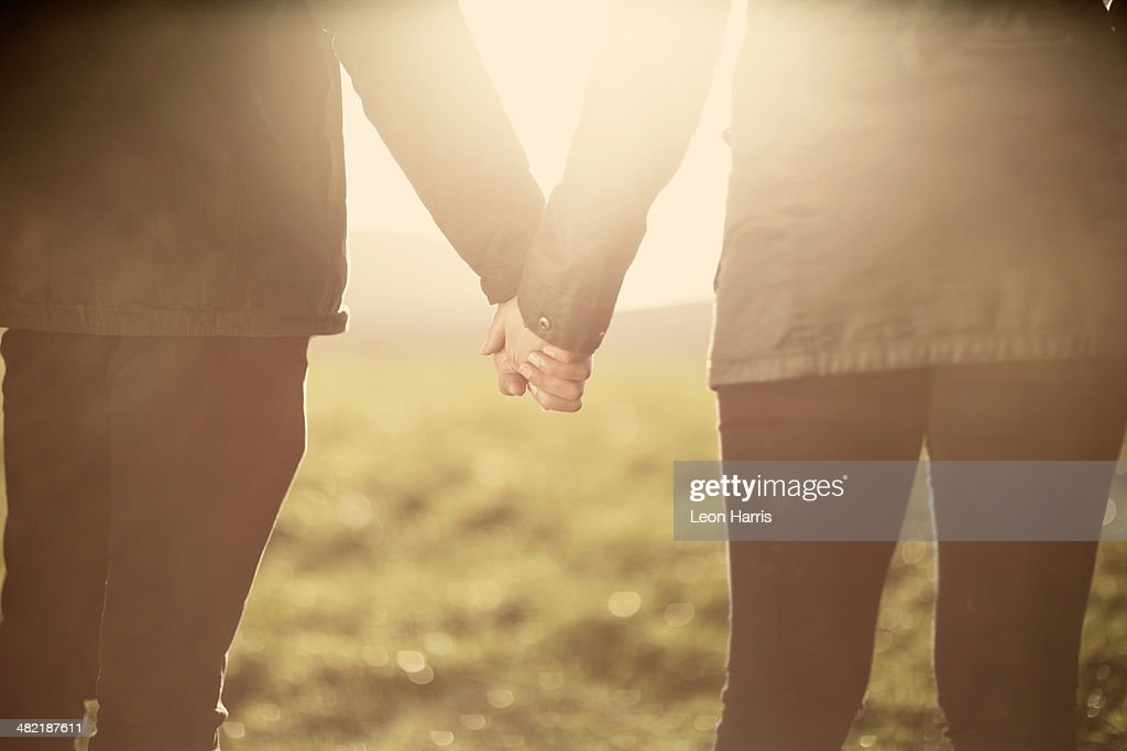 Mid section of couple, holding hands