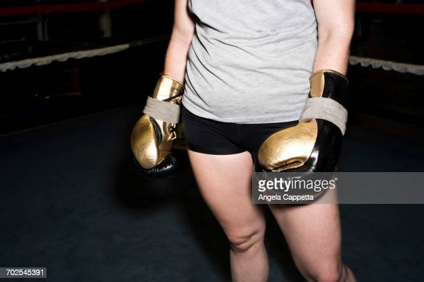 Mid section of female boxer in boxing ring wearing gold boxing gloves