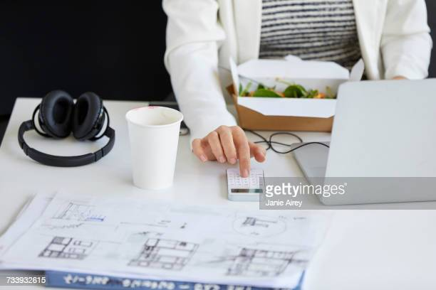 Mid section of female designer pressing smartphone keypad at office desk