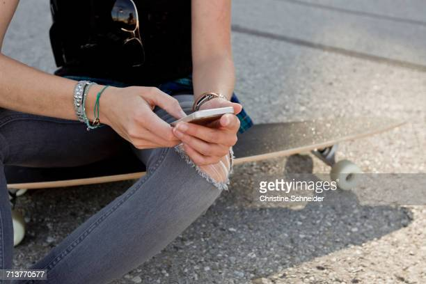 Mid section of female skateboarder sitting on skateboard texting on smartphone