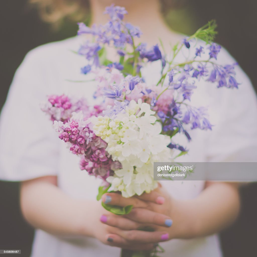 Mid section of girl (6-7) holding bouquet