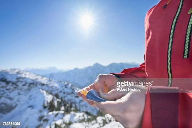 Mid section of man applying sun cream