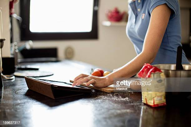 Mid section of woman looking for recipes in digital tablet at kitchen