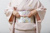 Mid section of woman wearing kimono, focus on obi sash