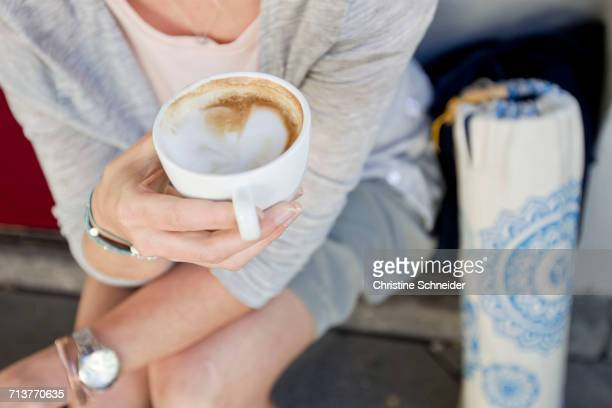 Mid section of woman with empty coffee cup at city sidewalk cafe