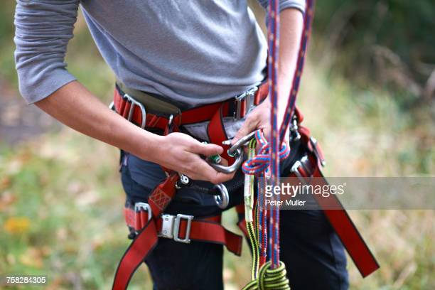 Mid section of young male trainee tree surgeon fastening safety harness