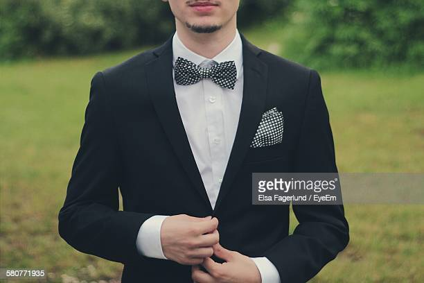Mid Section Of Young Man In Bow Tie Standing On Field