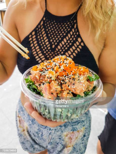 Mid section of young woman eating poke bowl at Hermosa Beach, California, USA