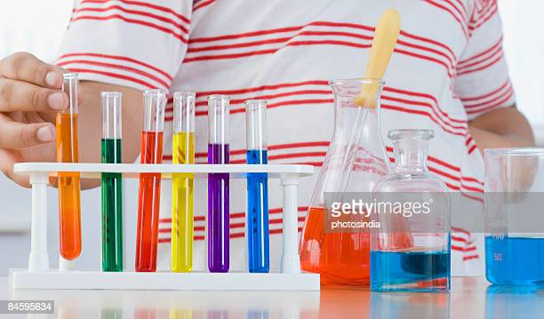 Mid section view of a boy putting a test tube in a test tube holder
