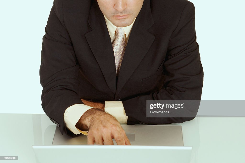 Mid section view of a businessman using a laptop : Foto de stock