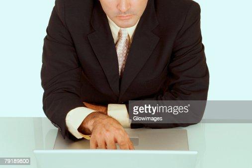 Mid section view of a businessman using a laptop : Foto de stock