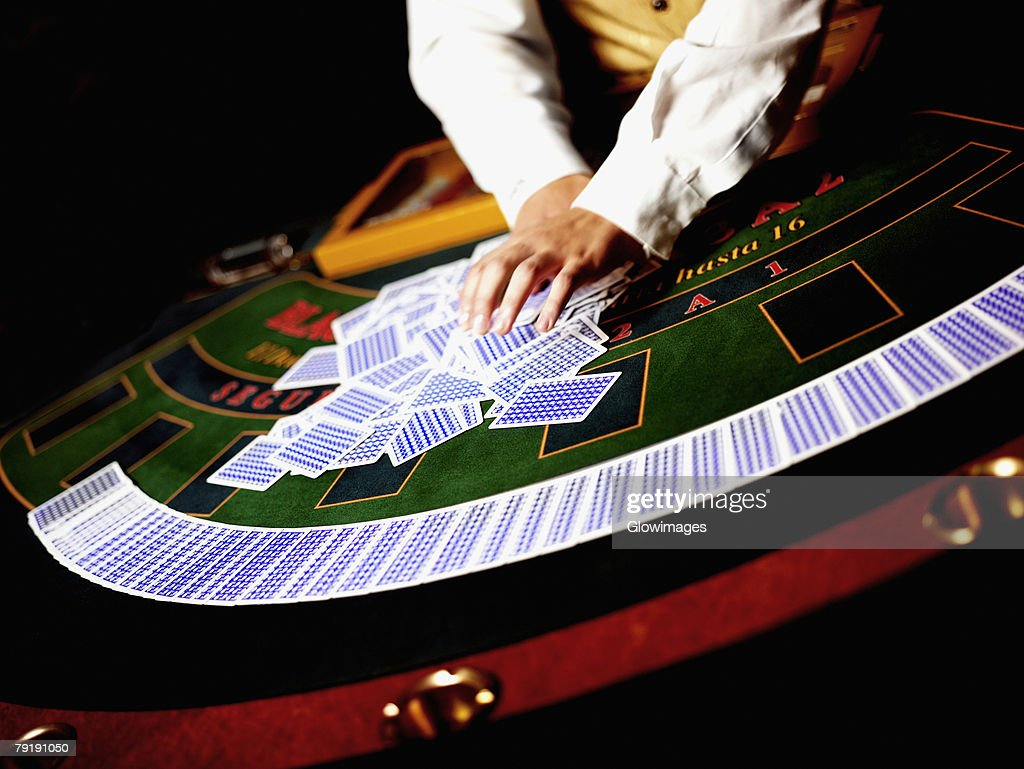 Mid section view of a casino worker shuffling playing cards on a gambling table : Foto de stock