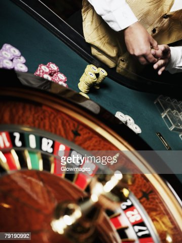 Mid section view of a casino worker standing at a roulette table : Foto de stock
