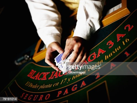 Mid section view of a casino worker's hand shuffling playing cards on a gambling table : Foto de stock