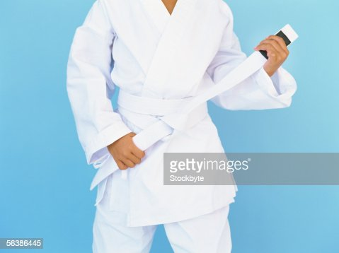 mid section view of a child tying the belt of his uniform : Stock Photo