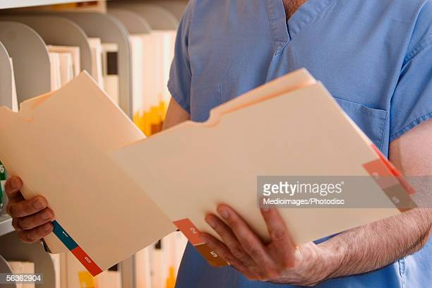 Mid section view of a doctor holding medical reports in a medical records room