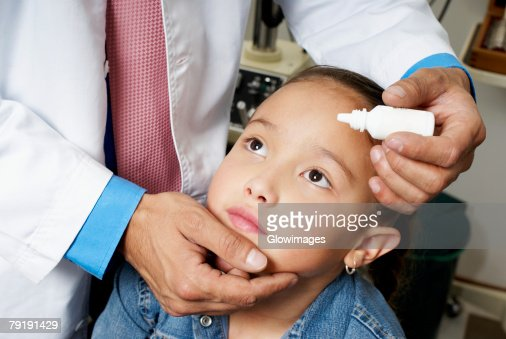 Mid section view of a doctor putting eye drops in a girl's eye : Foto de stock