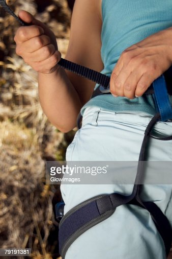 Mid section view of a female climber adjusting harness : Foto de stock