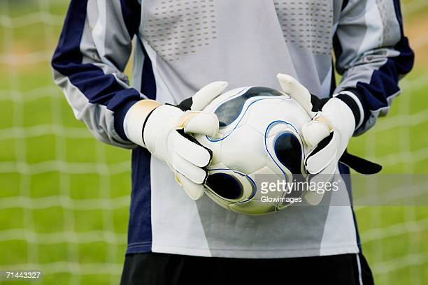 Mid section view of a goalie holding a soccer ball