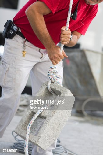 Mid section view of a male construction worker pulling a concrete block : Foto de stock