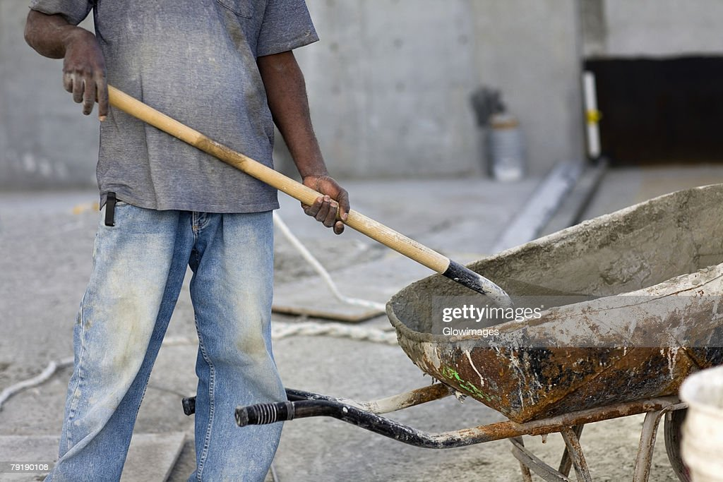 Mid section view of a male construction worker shoveling cement : Stock Photo
