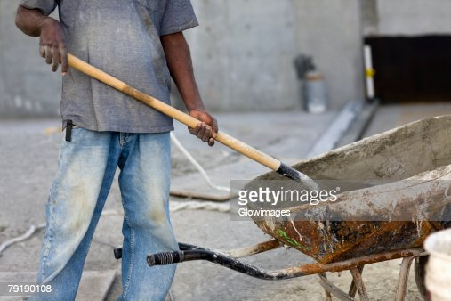 Mid section view of a male construction worker shoveling cement : Foto de stock