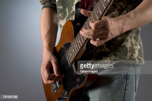 Mid section view of a male guitarist playing a guitar : Stock Photo
