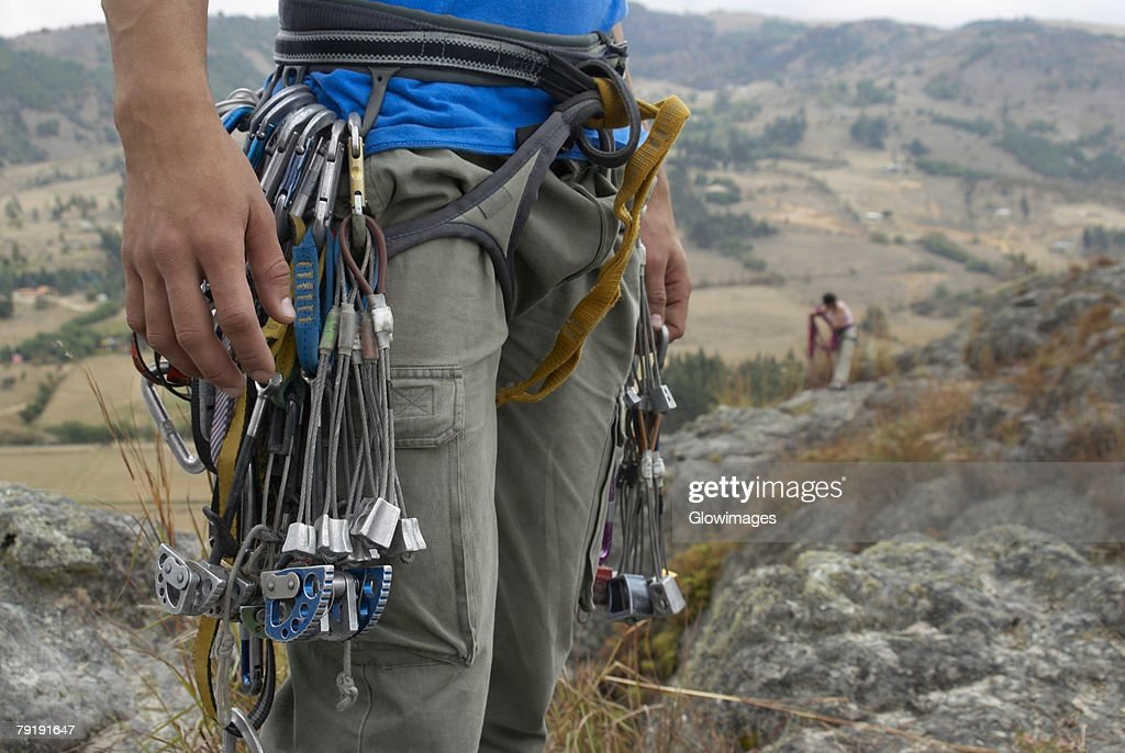 Mid section view of a male rock climber carrying rock climbing equipments : Foto de stock