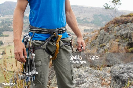 Mid section view of a male rock climber with climbing equipments around his waist : Foto de stock