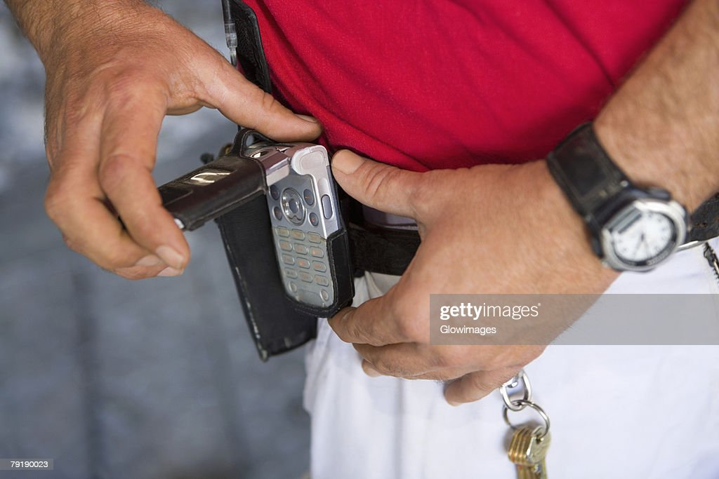 Mid section view of a man fastening a mobile phone on his belt : Foto de stock