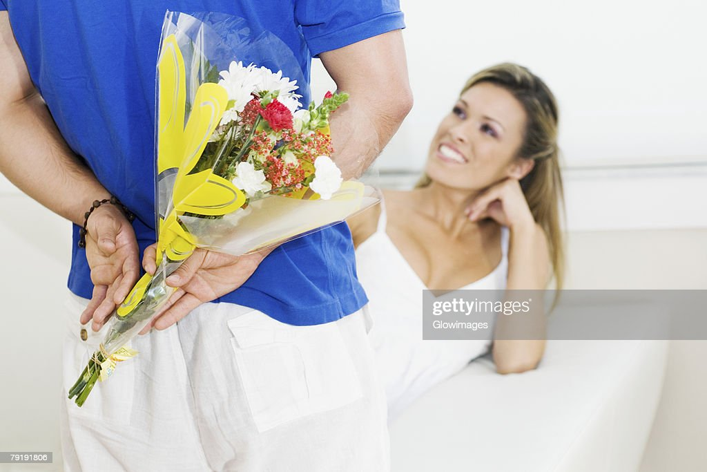 Mid section view of a man holding a bouquet of flowers behind his back with a young woman sitting on a couch and smiling : Stock Photo