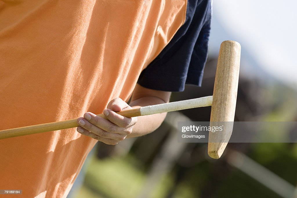 Mid section view of a man holding a polo mallet : Stock Photo