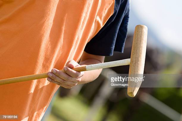Mid section view of a man holding a polo mallet