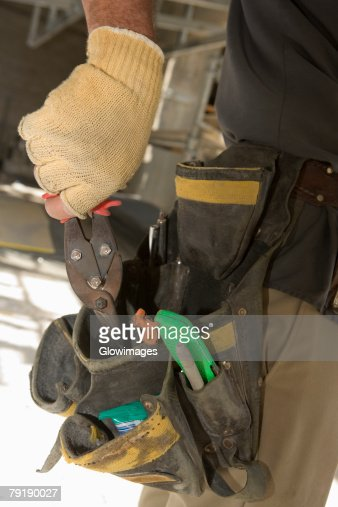Mid section view of a man putting pliers into a tool belt : Stock Photo