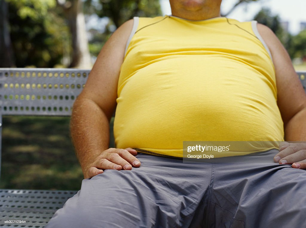 mid section view of a man sitting on a bench in a park : Stock Photo