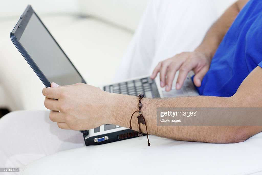 Mid section view of a man using a laptop : Foto de stock