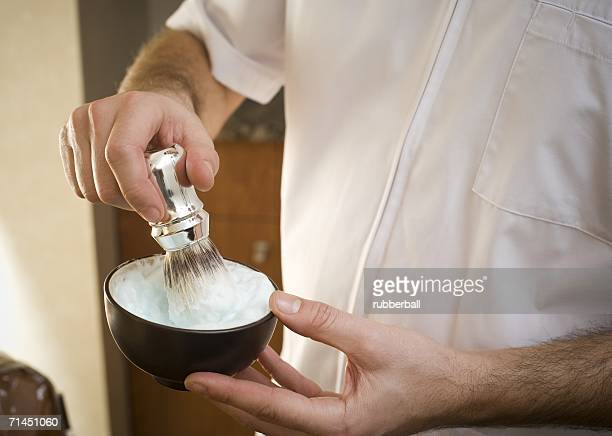 Mid section view of a man's hand mixing shaving cream with a brush in a bowl
