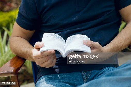Mid section view of a mid adult man holding a book : Stock Photo