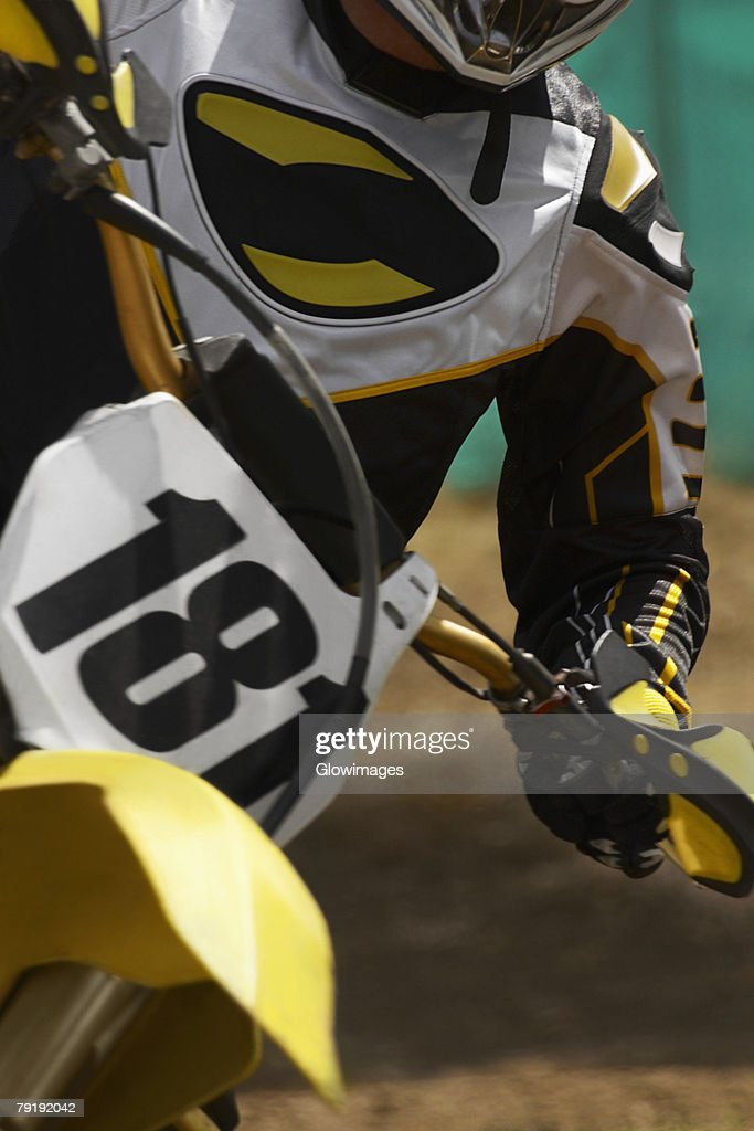 Mid section view of a motocross rider riding a motorcycle : Foto de stock
